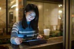 Asiatische junge Frau, die Tablette für das on-line-Einkaufen im Café verwendet lizenzfreie stockfotos