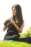 Asiatische junge Frau sitzen auf suchenden Ferngläsern des Hügels Lizenzfreie Stockfotos