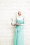asiatische junge Frau tragende hijab Stellung beim Halten eines Laptops Stockfotos