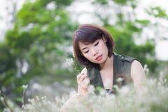 Asiatische junge Frauen, die auf Wiese sitzen Stockfotos