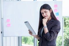 asiatische junge Geschäftsfrau, die Digital-Tablet-Computer lokalisiert auf Hintergrund des weißen Brettes im Büro hält lächelnde lizenzfreie stockfotos