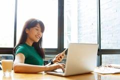 Asiatische junge InhaberGeschäftsfrau, die online, Post auf Laptoporganisierendem Arbeitsprozeß im Büro überprüfend arbeitet Kopi stockfoto