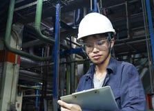 Asiatische junge Männer überprüfen die Maschine innerhalb der industriellen Fabrik stockfotos