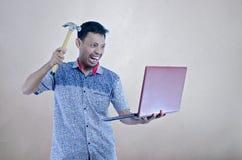 Asiatische junge Männer, die versuchen, einen Laptop durch Hummer zu brechen lizenzfreie stockfotos