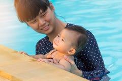 Asiatische junge Mutter und nettes Achtmonatebaby, die p schwimmend genießt Lizenzfreie Stockfotos