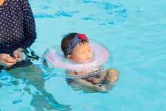 Asiatische junge Mutter und nettes Achtmonatebaby, die schwimmendes PO spielt Stockfoto