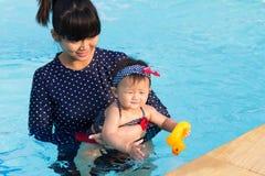 Asiatische junge Mutter und nettes Achtmonatebaby genießen Swimmingpool Lizenzfreies Stockfoto