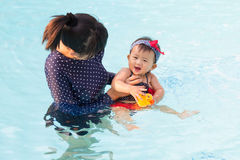 Asiatische junge Mutter und nettes Achtmonatebaby genießen Swimmingpool Stockfotografie