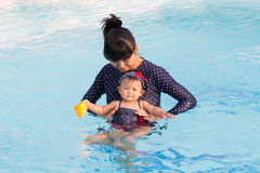 Asiatische junge Mutter und nettes Achtmonatebaby genießen Swimmingpool Lizenzfreie Stockfotografie