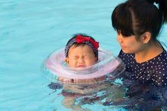 Asiatische junge Mutter und nettes Achtmonatebaby im Swimmingpool Stockbilder