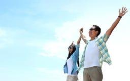 Asiatische junge Paarstellung und angehoben ihren Händen zum Himmel Stockfotografie