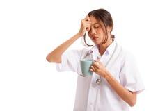 Asiatische junge Ärztin erhielt Kopfschmerzen mit einem Tasse Kaffee Stockbild