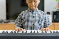 Asiatische Jungen an den verletzten Händen, die das Klavier, Klavier lernend spielen Stockbild