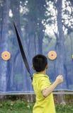 Asiatische Jungen sind Bogenschie?en im Lagerabenteuer lizenzfreies stockfoto