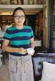 Asiatische Kellnerin, die das Kaffeetasselächeln hält Stockfotografie
