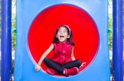 Asiatische Kinder des glücklichen Lächelns auf Kreis Plastik-tennel Spielparks stockfotografie