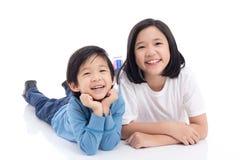 Asiatische Kinder, die auf dem weißen Hintergrund lokalisiert liegen Stockfoto