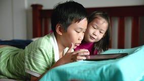 Asiatische Kinder, die digitale Tablette verwenden Verschieben Sie Fokus Asiatische Kinder, die digitale Tablette verwenden Glück stock video footage