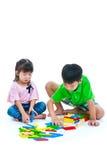 Asiatische Kinder, die hölzerne Blöcke des Spielzeugs, auf Weiß spielen Stockfotografie