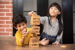 Asiatische Kinder spielen Holzklotzstapelspiel zusammen stockbilder