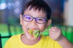 Asiatische Kinder tragen Gläser mit dem blockierenden und essenden Blaulicht Stockbilder