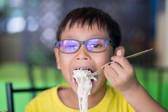 Asiatische Kinder tragen Gläser mit dem blockierenden und essenden Blaulicht Lizenzfreie Stockbilder