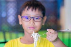 Asiatische Kinder tragen Gläser mit dem blockierenden und essenden Blaulicht Lizenzfreies Stockfoto