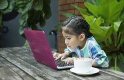 Asiatische Kinder unter Verwendung des Laptops und der Kaffeetasse auf hölzerner Tabelle stockfotografie