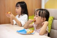Asiatische kleine chinesische Schwestern, die Pizza essen Lizenzfreie Stockfotos