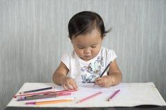 Asiatische Kleinkind/das Baby hat Spaß lernend, Bleistifte zu benutzen Stockfotos