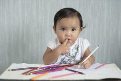Asiatische Kleinkind/das Baby hat Spaß lernend, Bleistifte zu benutzen Stockbilder