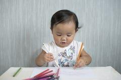 Asiatische Kleinkind/das Baby hat Spaß lernend, Bleistifte zu benutzen Lizenzfreie Stockfotos