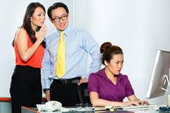 Asiatische Kollegen, die Angestellten angreifen oder einschüchtern lizenzfreies stockfoto