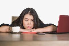 Asiatische koreanische Geschäftsfrau, die im Druck an überwältigter und frustrierter leidender Krise des Bürocomputertisch-Gefühl lizenzfreies stockbild