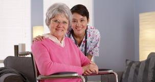 Asiatische Krankenschwester, die mit älterem Patienten lächelt Stockbild