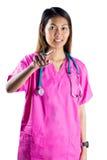 Asiatische Krankenschwester mit Stethoskop zeigend vor ihr Lizenzfreie Stockfotografie