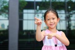 Asiatische Lage des kleinen M?dchens, die dazu ihren Zeigefinger mit nettem L?cheln zeigt lizenzfreie stockfotografie