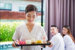 Asiatische lächelnde Masseuse, die einen Behälter am Badekurort hält Stockbild