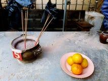 Asiatische Leute bieten Räucherstäbchen, Lebensmittel, Frucht und Getränk dem Respektieren oder Wunsch Buddha-Statue, tote Famili Lizenzfreie Stockfotografie