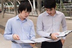 Asiatische Leute des Geschäfts, die über Bericht im b stehen und sprechen lizenzfreie stockfotografie