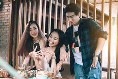 Asiatische Leute, die Spaß während unter Verwendung des Smartphone im Restaurant haben stockbild