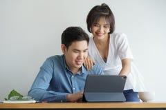 Asiatische Liebespaare sitzen Stuhl im Wohnzimmer und das Arbeiten auf Tablette, die sie glücklich lächeln lizenzfreies stockbild