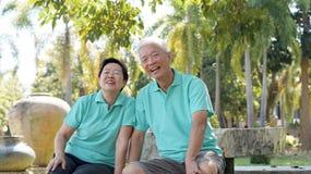 Asiatische ältere Paare, die im Park sich entspannen Lizenzfreie Stockfotos