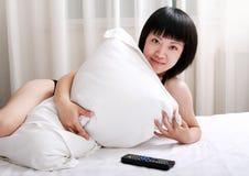Asiatische Mädchen, die auf Bett liegen Lizenzfreie Stockbilder