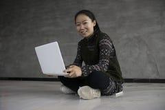 Asiatische Mädchen, die auf dem Boden unter Verwendung der Laptops sitzen Stockbilder