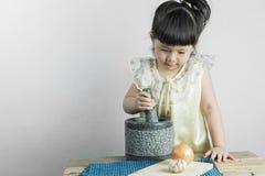 Asiatische Mädchen sind, glücklich kochend und auf grauem Hintergrund mit Raum Stockbild