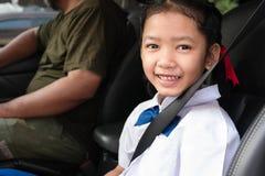 Asiatische Mädchenabnutzungsuniform sitzen im Auto lizenzfreie stockfotos