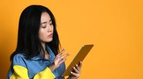 Asiatische Mädchengebrauchsauflage zu Hause, Konzept der Technologie, Funktion, Internet usw. stockfotografie