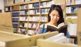 Asiatische Mädchenlesung in einer Buchhandlung lizenzfreies stockbild