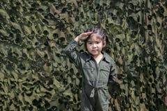 Asiatische Mädchenrespekt-Soldataktion mit grüner Soldat- oder Pilotuno lizenzfreies stockfoto